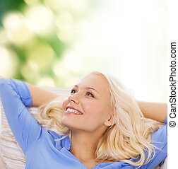 smiling young woman lying on sofa - relaxing and happiness...