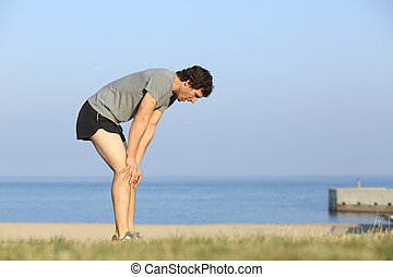 Exhausted runner man resting on the beach after workout with...