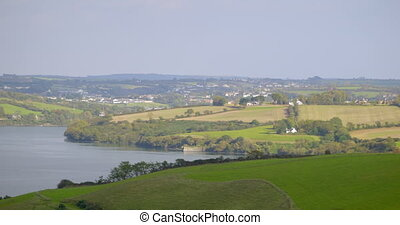 Panoramic shot of green fields and lake in the countryside