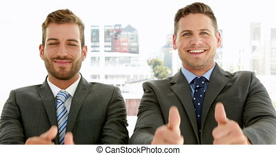 Smiling businessmen looking at camera giving thumbs up in...