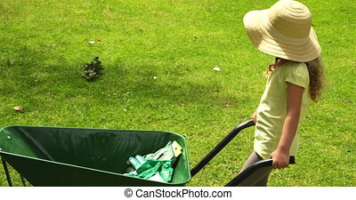 Cute girl pushing a wheelbarrow on a sunny day