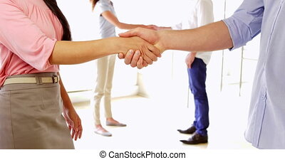 Young coworkers shaking hands in the office