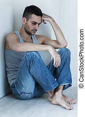 Depressed and hopeless. Depressed young man sitting on the floor and holding head in hand