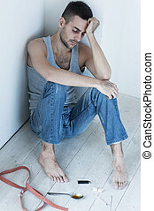 Depression and hopelessness. Depressed young man sitting on the floor and holding head in hand while syringe and spoon laying near him