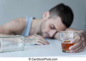 Forgetting his problems. Young man sitting at the table with empty bottle on it and keeping eyes closed