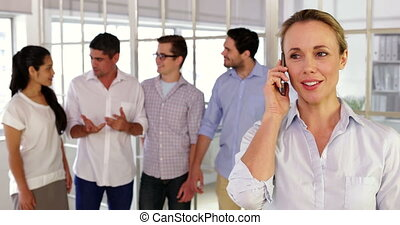 Female designer phoning before posing in the office