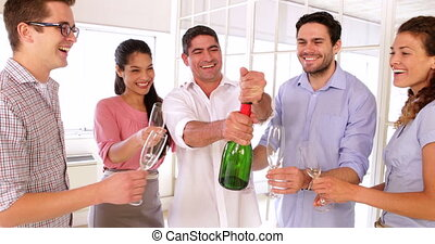 Cheerful colleagues celebrating with champagne in the office
