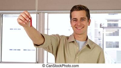 Handsome businessman showing his keys