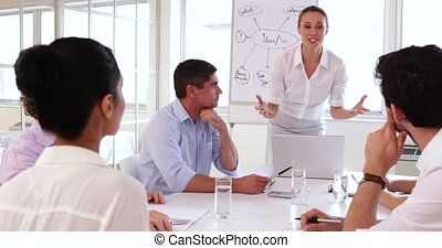 Cheerful businesswoman talking to business team in the...