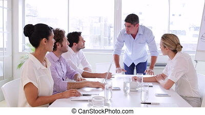 Boss giving instructions to his team in the office