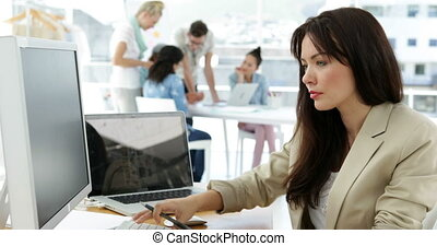 Woman working at her desk and smiling at camera in creative...