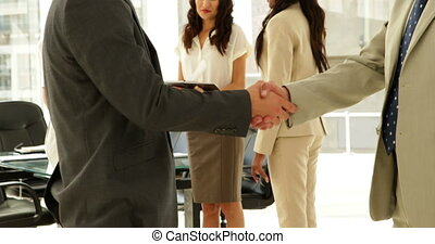 Businessmen talking together and shaking hands at the office