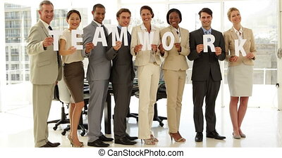 Happy business people holding letters spelling 'teamwork'