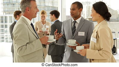 Business people chatting at a conference having coffee at...