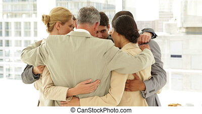 Business people hugging each other in a circle at the office