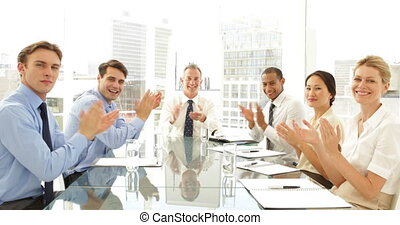 Business people clapping at presentation at the camera at...