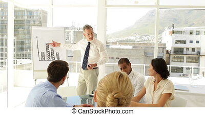 Businessman explaining bar chart to his staff at...
