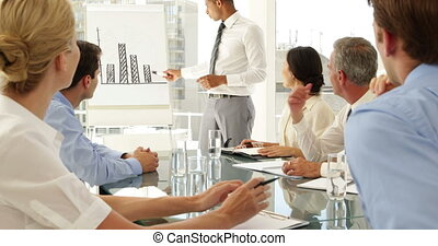 Businessman explaining bar chart to colleagues at...