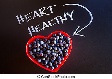 Fresh picked organic blueberries in red heart shaped bowl...