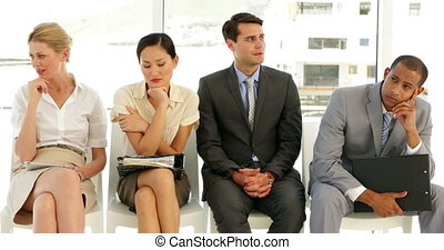 Business people waiting for an interview in a row at the...
