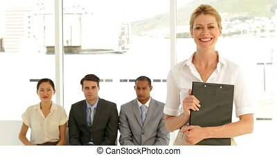 Businesswoman giving thumbs to camera in front of applicants...
