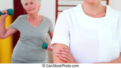 Physical therapist smiling at camera with patient dancing in...