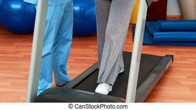 Physical therapist showing patient how to use treadmill at...