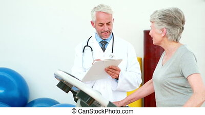 Doctor watching patient using treadmill at the...