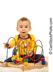 Happy toddler boy playing with wooden toy and sitting on fur...