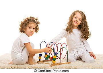 Happy girls playing with wooden toy