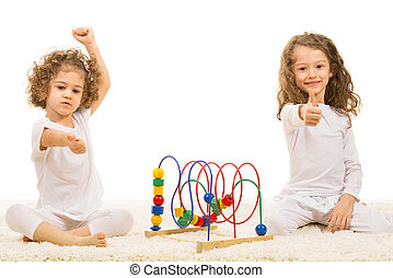Girls with wooden toy giving thumbs up