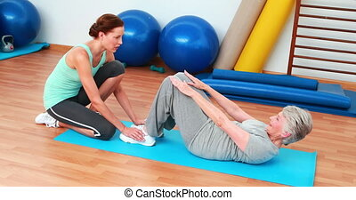 Trainer helping her elderly client do sit ups at the...