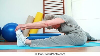Elderly woman touching her toes on exercise mat at the...