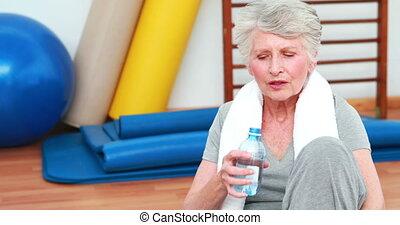 Elderly woman sitting on floor drinking water at the...