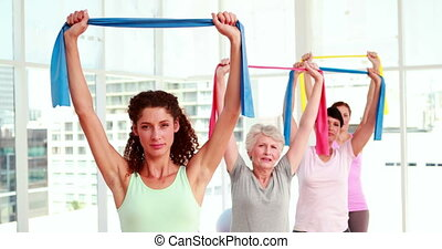 Women stretching resistance bands - Women stretching...