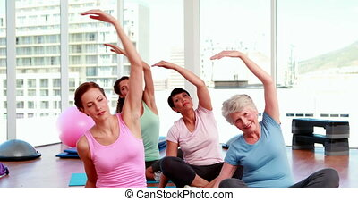 Smiling women doing yoga in fitness studio at the gym