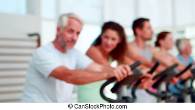 Happy group doing a spinning class