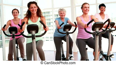 Women in doing a spinning class - Group of smiling women in...