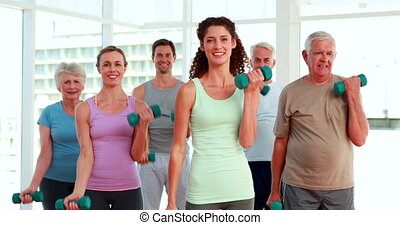 Fitness group lifting hand weights at the gym