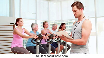 Spinning instructor smiling at camera in front of his class...