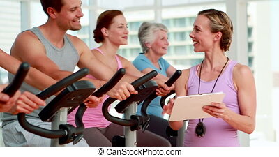 Happy group doing a spinning class at the gym