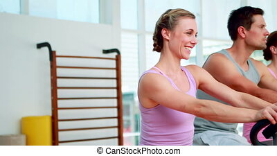 Happy fitness group doing a spinning class at the gym