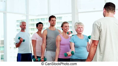 Fitness group lifting hand weights watching instructor at...