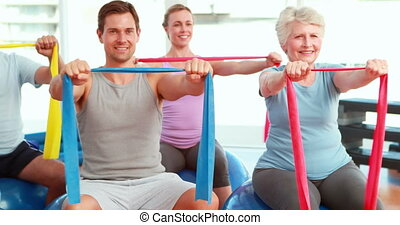 Group sitting on exercise balls stretching resistance bands...