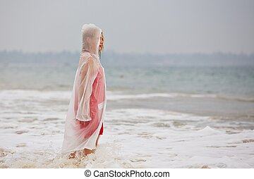 Heavy rain - Young woman on the beach in heavy rain