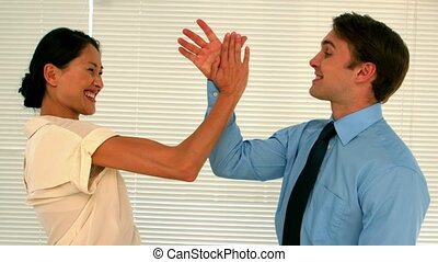 Business people high fiving in the - Business people high...