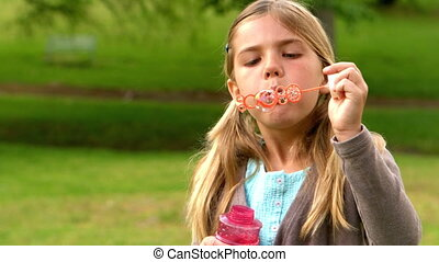 Little girl blowing bubbles in the park in slow motion