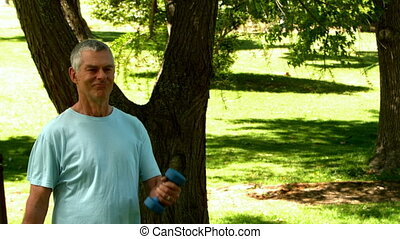 Senior man lifting hand weights in the park in slow motion