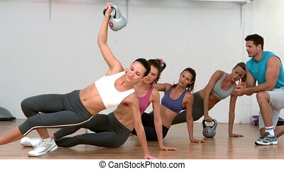 Fitness class lifting kettle bells together in side plank in...