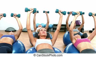 Fitness class lifting hand wieights on exercise balls in...